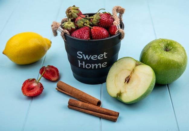 青色の背景に緑のリンゴとシナモンスティックのバスケットにイチゴのトップビュー