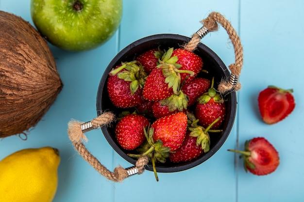 파란색 배경에 코코넛과 딸기 조각과 바구니에 딸기의 상위 뷰