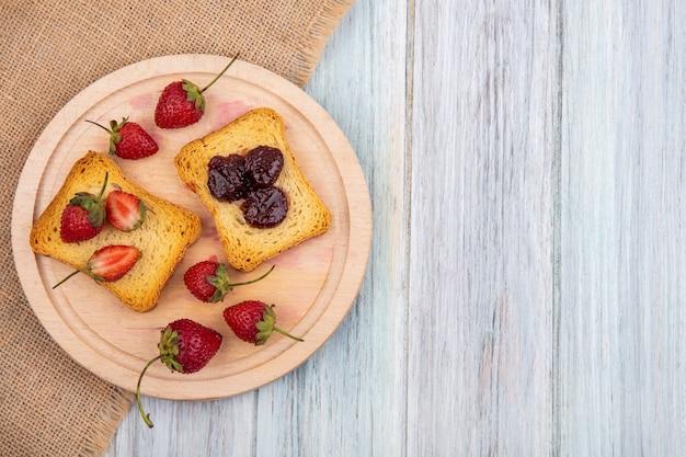 コピースペースを持つ灰色の木製の背景に袋布の木製キッチンボード上のイチゴのトップビュー