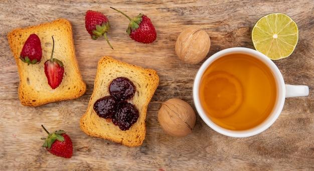 木製の背景にライムと紅茶のカップとパンにイチゴのトップビュー