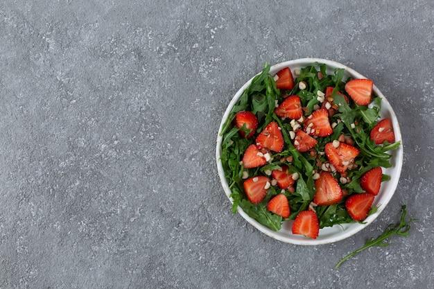 明るい灰色の背景にルッコラとイチゴのサラダのトップ ビュー