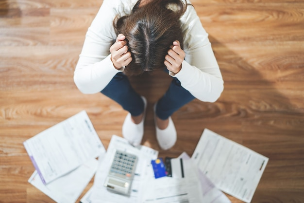 クレジットカードの借金を支払うためにお金を見つけようとしているストレスの多い若い女性の上面図。