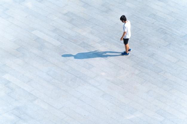 歩道橋を歩いているファッションクロスとスポーツウェアを持つ学生の上面図
