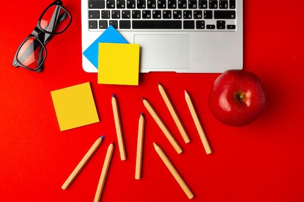 開いているノートパソコンと赤いリンゴ、その他の消耗品と学生の作業スペースの平面図