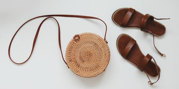 Вид сверху стильных женских сандалий и плетеной сумки из ротанга, изолированной на белом
