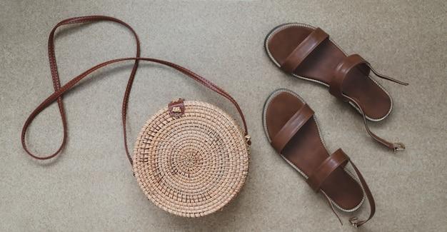 Вид сверху на стильные женские босоножки и плетеную сумку из ротанга
