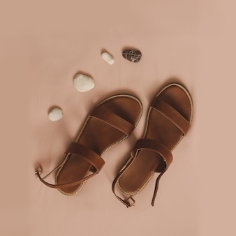 Вид сверху стильных женских сандалий с морской галькой на бежевом фоне отдыха на море концепции