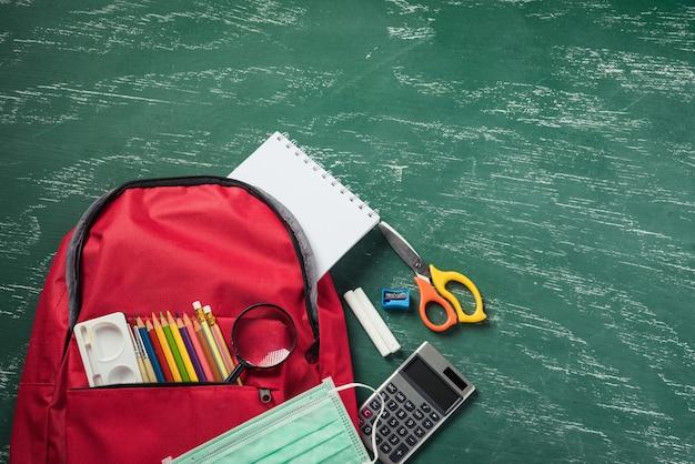Вид сверху стильного красного школьного рюкзака на зеленой доске с защитной маской