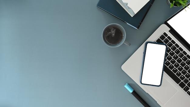 파란색 테이블에 노트북 컴퓨터와 스마트 폰이 있는 세련된 작업 공간의 최고 전망. 문자 메시지 또는 정보 콘텐츠를 위한 공간을 복사합니다.