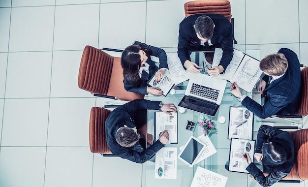 オフィスの職場で新しいマーケティングスキームを議論している成功したビジネスチームの上面図。写真はあなたのテキストの空白スペースです。