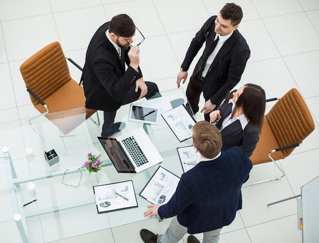 Вид сверху успешной бизнес-команды, обсуждающей маркетинговую графику на семинаре в современном офисе. на фотографии есть пустое место для вашего текста.