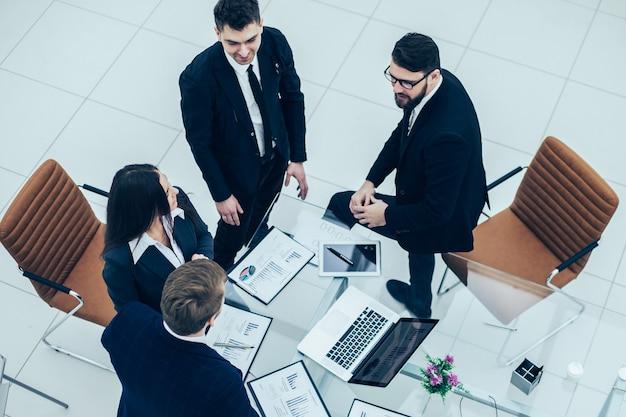 Вид сверху успешной бизнес-команды, обсуждающей маркетинговую графику на семинаре в современном офисе
