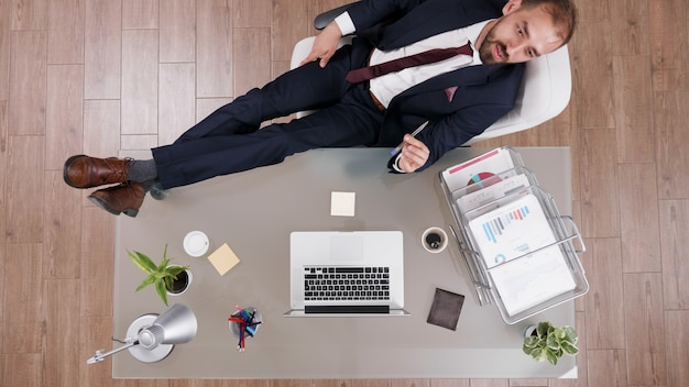 会社の投資のアイデアをブレインストーミングする机の上に彼の足で立っているスーツで成功した実業家の上面図。スタートアップ企業のオフィスでビジネス戦略に取り組んでいるエグゼクティブマネージャー