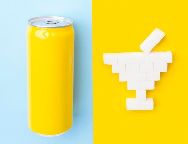 Вид сверху на кубики сахара в форме коктейльного бокала и банку для безалкогольных напитков