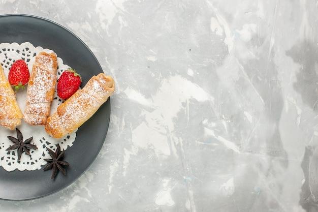 白い机の上にイチゴと砂糖粉ベーグルおいしい生地の上面図