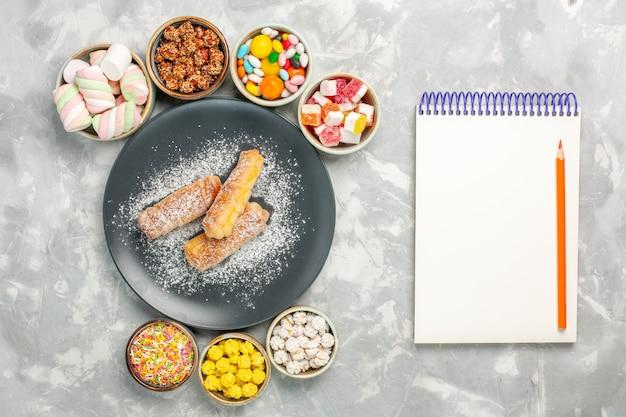 흰색 표면에 사탕과 마시맬로와 설탕 가루 베이글의 상위 뷰