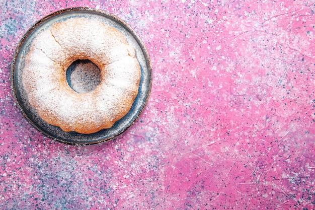 Вид сверху сахарной пудры круглый сформированный на светло-розовой поверхности