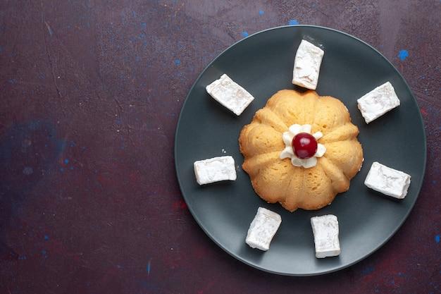 어두운 표면에 접시 안에 케이크와 함께 설탕 가루 사탕 맛있는 누가의 상위 뷰