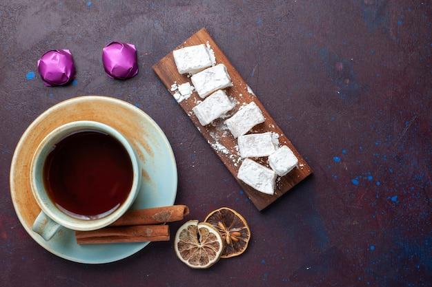 어두운 표면에 차와 설탕 가루 사탕 맛있는 누가의 상위 뷰