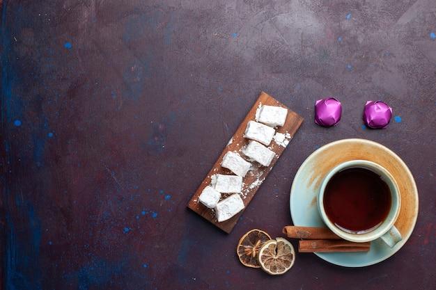 Вид сверху сахарной пудры, вкусной нуги с чаем на темной поверхности