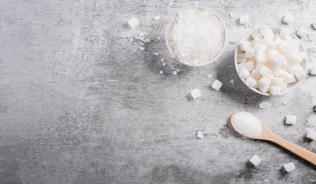 그릇에 있는 설탕의 상위 뷰와 혈액 내 당뇨병 조절의 상징인 숟가락