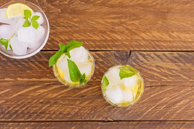 Вид сверху летних охлаждающих напитков на деревянном столе. свежий лимонад coolig с лаймом, лимоном, листьями мяты и льдом.