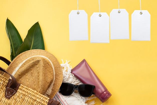 여름 휴가 용품 및 흰색 빈 태그의 상위 뷰 노란색 벽에 모자 태양 안경 자외선 차단제 크림과 비치 가방