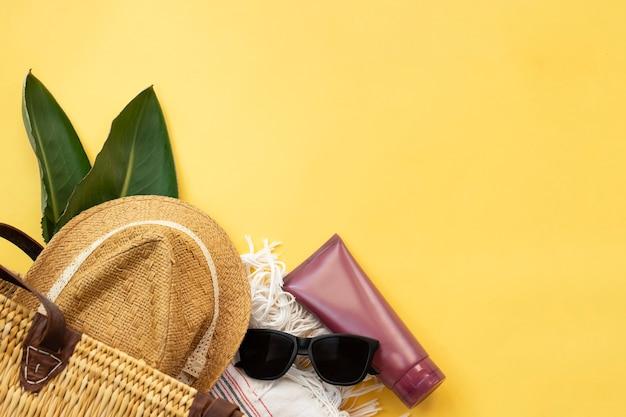여름 휴가의 상위 뷰는 노란색 벽에 모자 태양 안경 선 스크린 크림과 비치 가방을 제공합니다