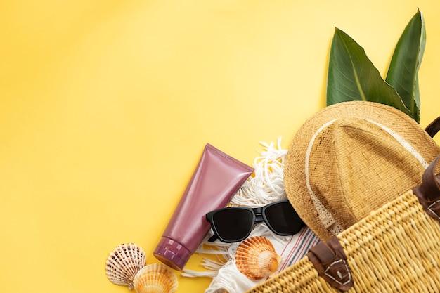 Вид сверху на принадлежности для летних каникул шляпа солнцезащитные очки солнцезащитный крем и пляжная сумка на желтой стене