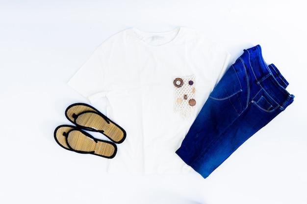 白い背景の上の夏の女性のジーンズ、tシャツ、サンダルの平面図です。夏のファッションコンセプト。フラットレイ