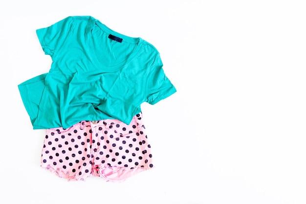 白い背景の上の夏の女性のショートパンツとtシャツの上面図。夏のファッションコンセプト。フラットレイ