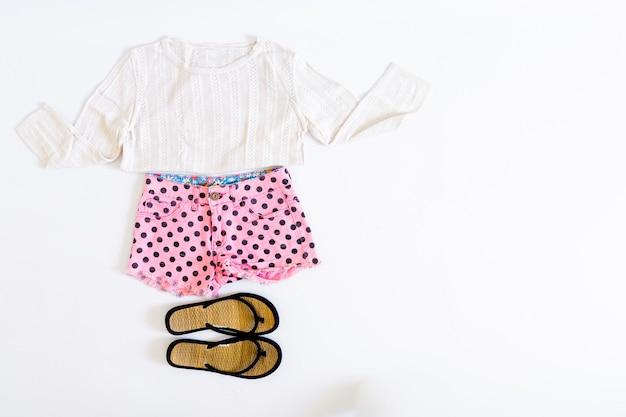 白い背景の上の夏の女性のショートパンツ、tシャツ、サンダルの平面図です。夏のファッションコンセプト。フラットレイ