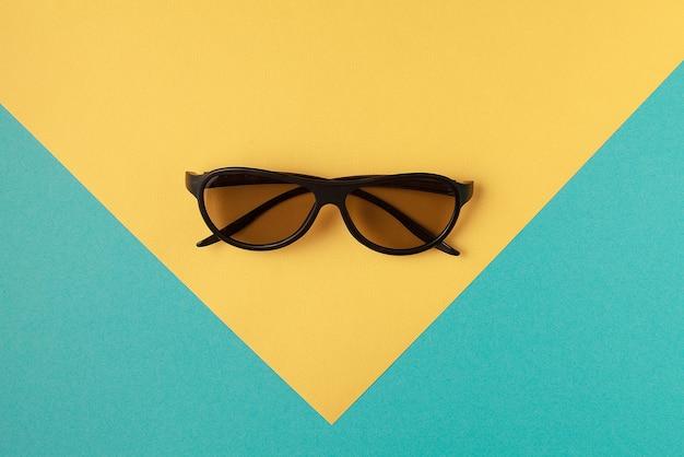 Вид сверху солнцезащитных очков на цветном фоне