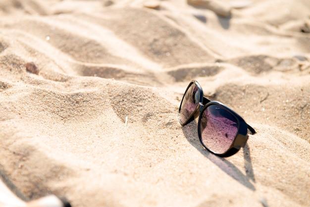 태양에 모래 검은 선글라스와 푸른 바다 근처 해변에서 선글라스의 상위 뷰