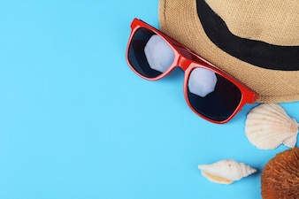 Top view of sunglasses, shells, starfish and hat