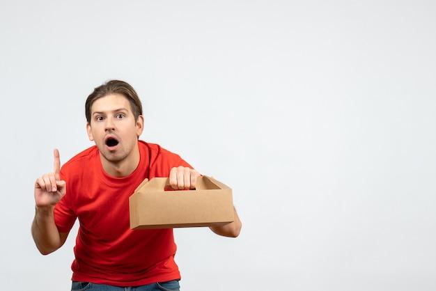 Вид сверху удивленного и эмоционального молодого человека в красной блузке, держащего коробку и указывающего вверх на белой стене