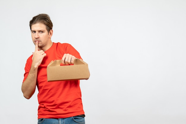 Вид сверху удивленного и эмоционального молодого человека в красной блузке, держащего коробку в глубоких мыслях на белой стене