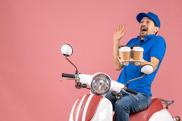 파스텔 복숭아에 주문을 들고 스쿠터에 앉아 모자를 쓰고 의료 마스크에 놀란 택배 남자의 상위 뷰