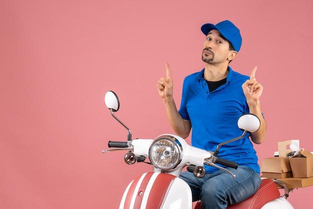 パステルピーチの上を指し示す注文を配達するスクーターに座っている帽子をかぶった驚いた宅配業者のトップビュー
