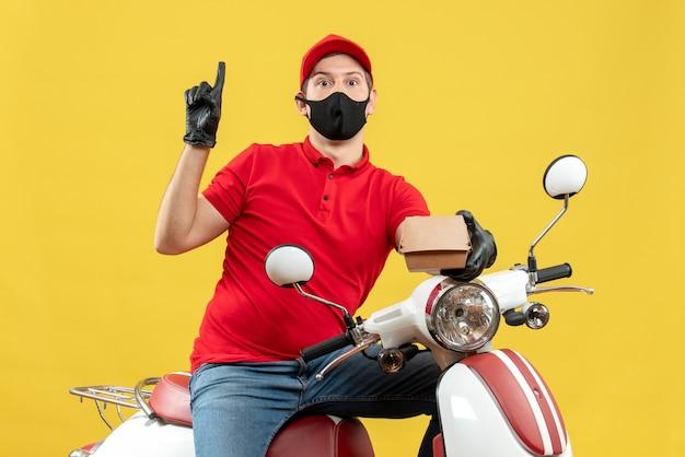上向きの順序を保持しているスクーターに座っている医療用マスクで赤いブラウスと帽子の手袋を着用して驚いた宅配便の男の上面図