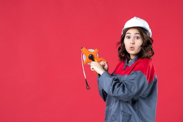 孤立した赤い背景に測定テープを保持しているハード帽子と制服を着て驚いた女性建築家の上面図