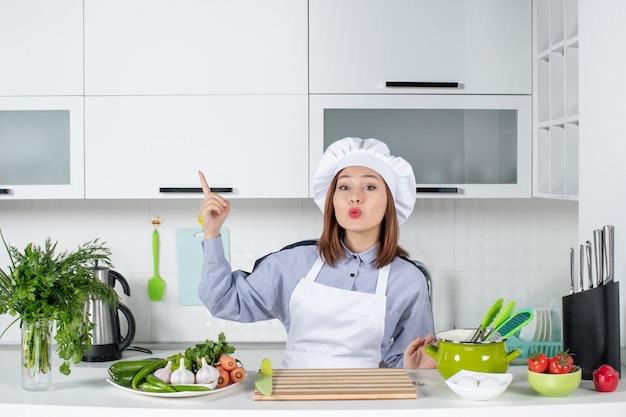 白いキッチンの右側に立っている驚いた女性シェフと新鮮な野菜の上面図
