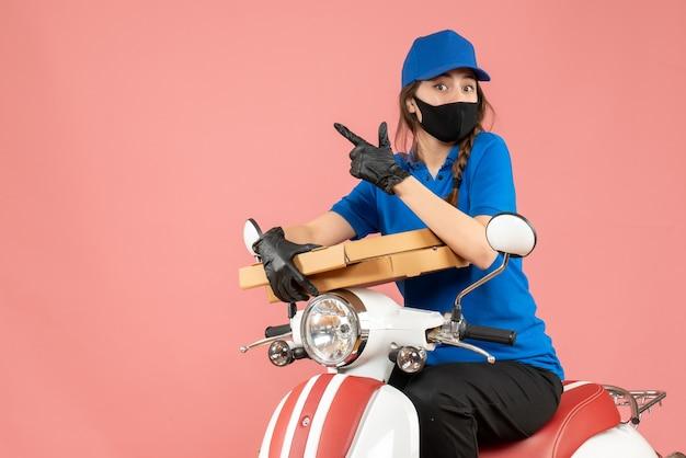 医療用マスクと手袋をはめた驚く女性宅配便業者がスクーターに座り、パステルピーチの上を指し示す注文を届けるトップビュー