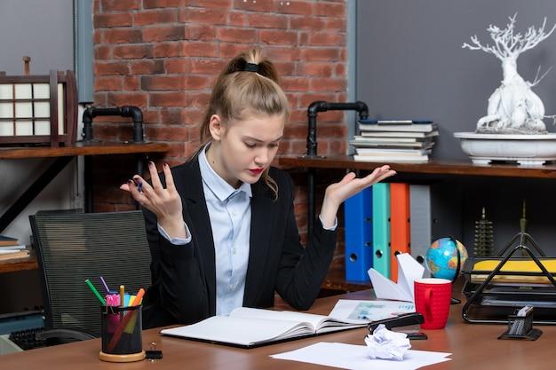 テーブルに座って、オフィスで慎重に何かに焦点を当てて驚いた女性の上面図