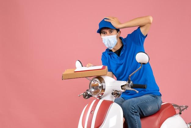 Вид сверху удивленного доставщика-мужчины в маске в шляпе, сидящего на скутере, доставляющего заказы, держа документ на персике