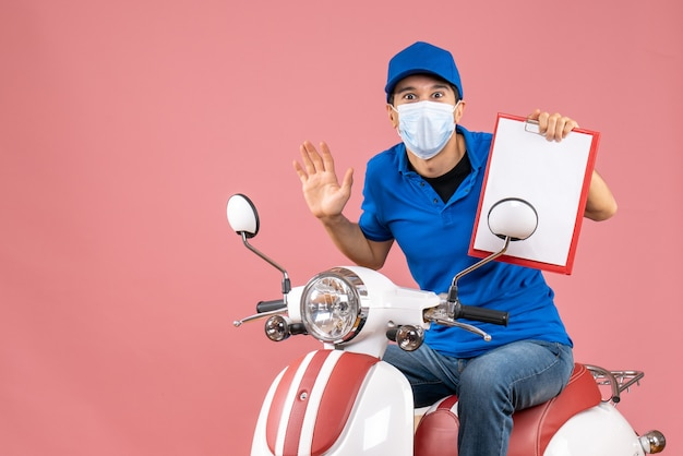 Вид сверху удивленного доставщика-мужчины в маске в шляпе, сидящего на скутере, показывая документ на пастельном персике