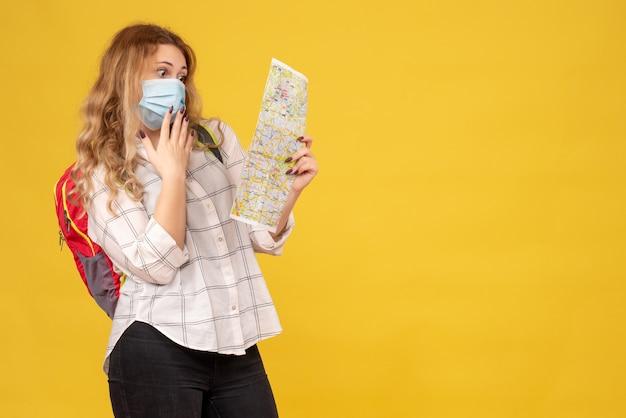 彼女のマスクと黄色の地図を見てバックパックを身に着けている驚いた旅行の女の子の上面図