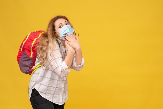 Вид сверху удивленной путешествующей девушки в маске и рюкзаке на желтом