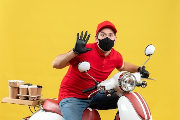 黄色の壁に5つを示すスクーターに座って注文を配信医療マスクで赤いブラウスと帽子の手袋を身に着けている驚いた若い大人の上面図