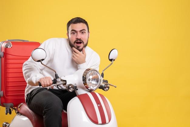 黄色のスーツケースを持ってオートバイに座っている驚いた若い男のトップ ビュー